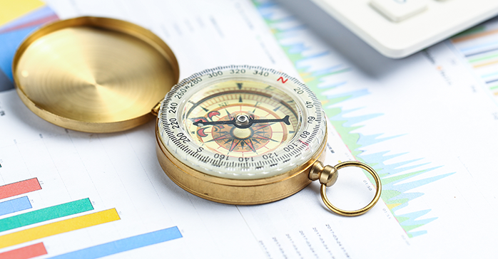 Compass on financial papers indicating a decision - cfa vs. caia - Schweser