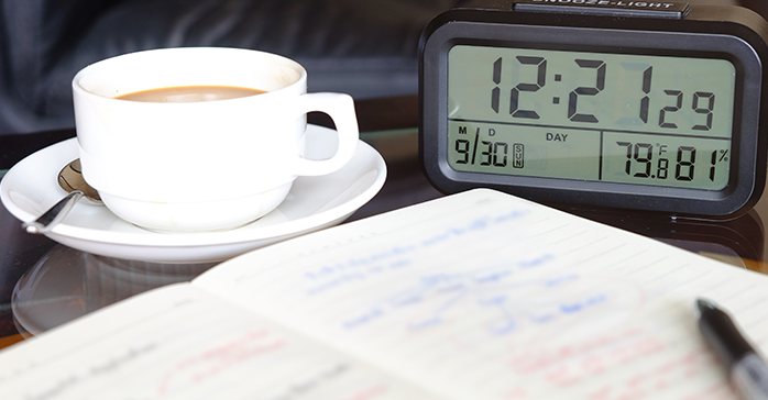 Notes, coffee, and clock for studying for CFA Exam while working full time
