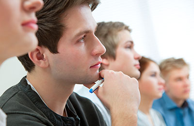 Students listening to an instructor in a live class.