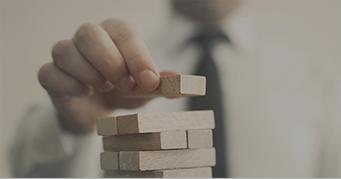 stacking wooden block that represent traits of CFA charterholders - Kaplan Schweser