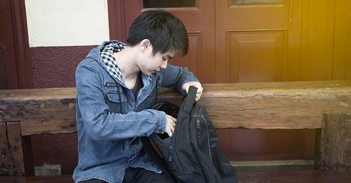Man checking his backpack at train station to make sure he has the items he needs for the CFA Exam