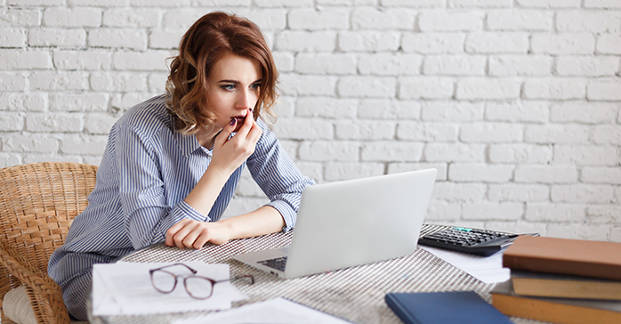 Woman looking at her CFA Exam results on her laptop- Kaplan Schweser