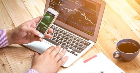Person analyzing stock information on a laptop and phone - Kaplan Schweser
