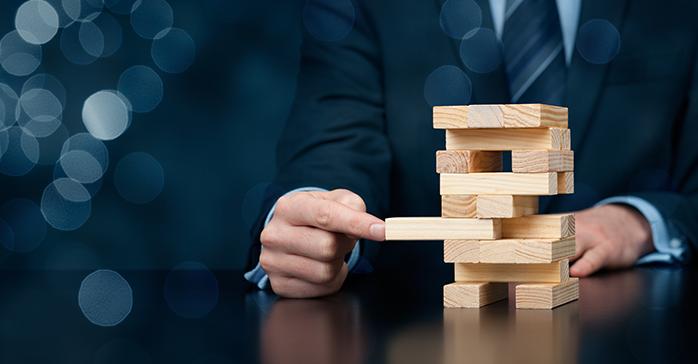 Man analyzing risk of move in Jenga game - Kaplan Schweser